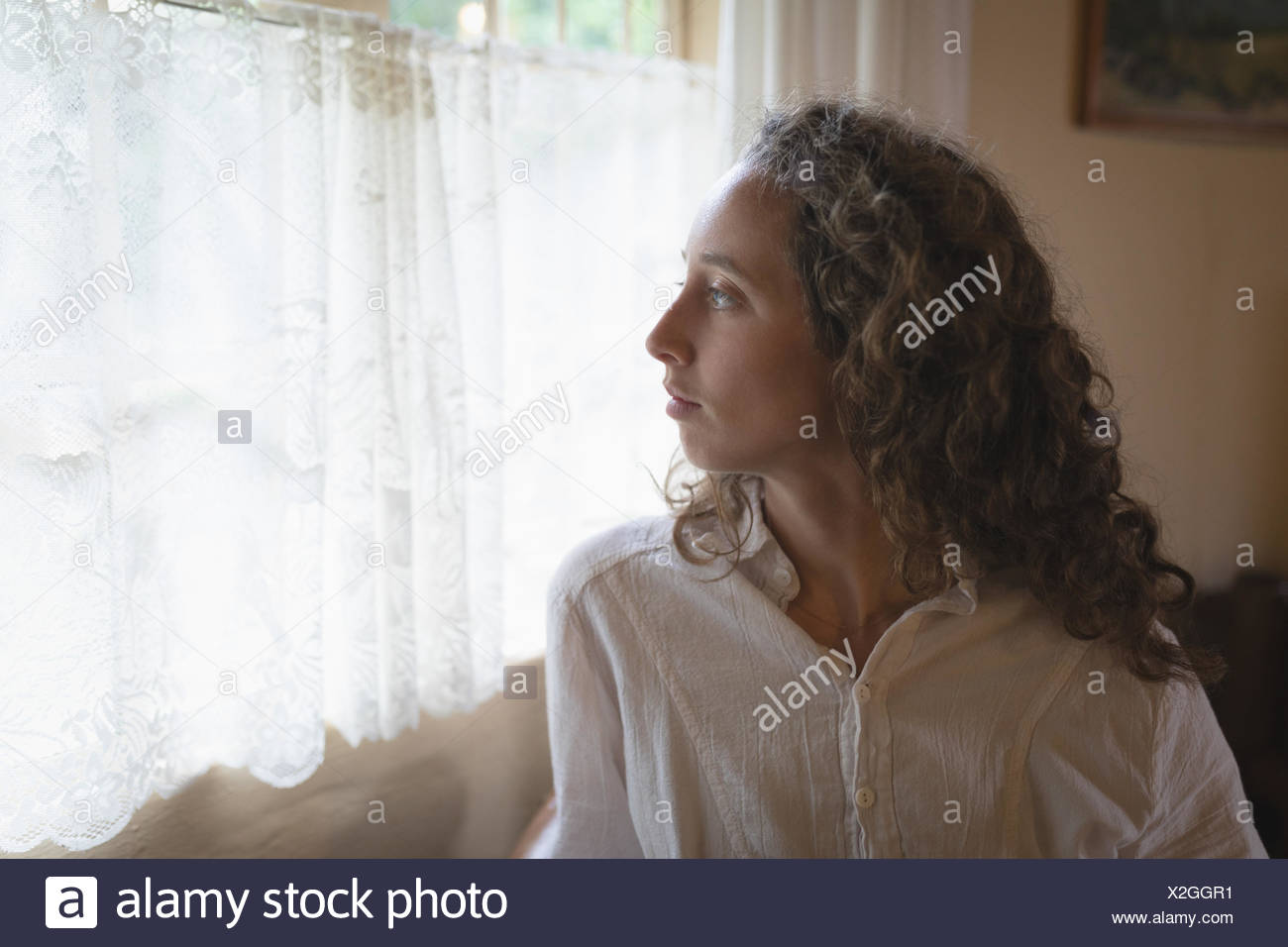 Frau, die durch Fenster im Wohnzimmer Stockbild