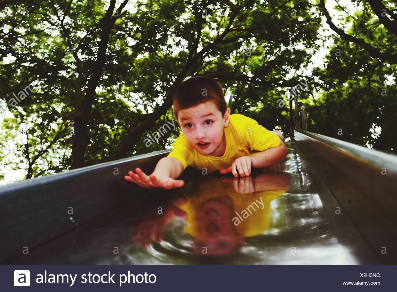Junge gleiten auf Folie im Park Stockbild