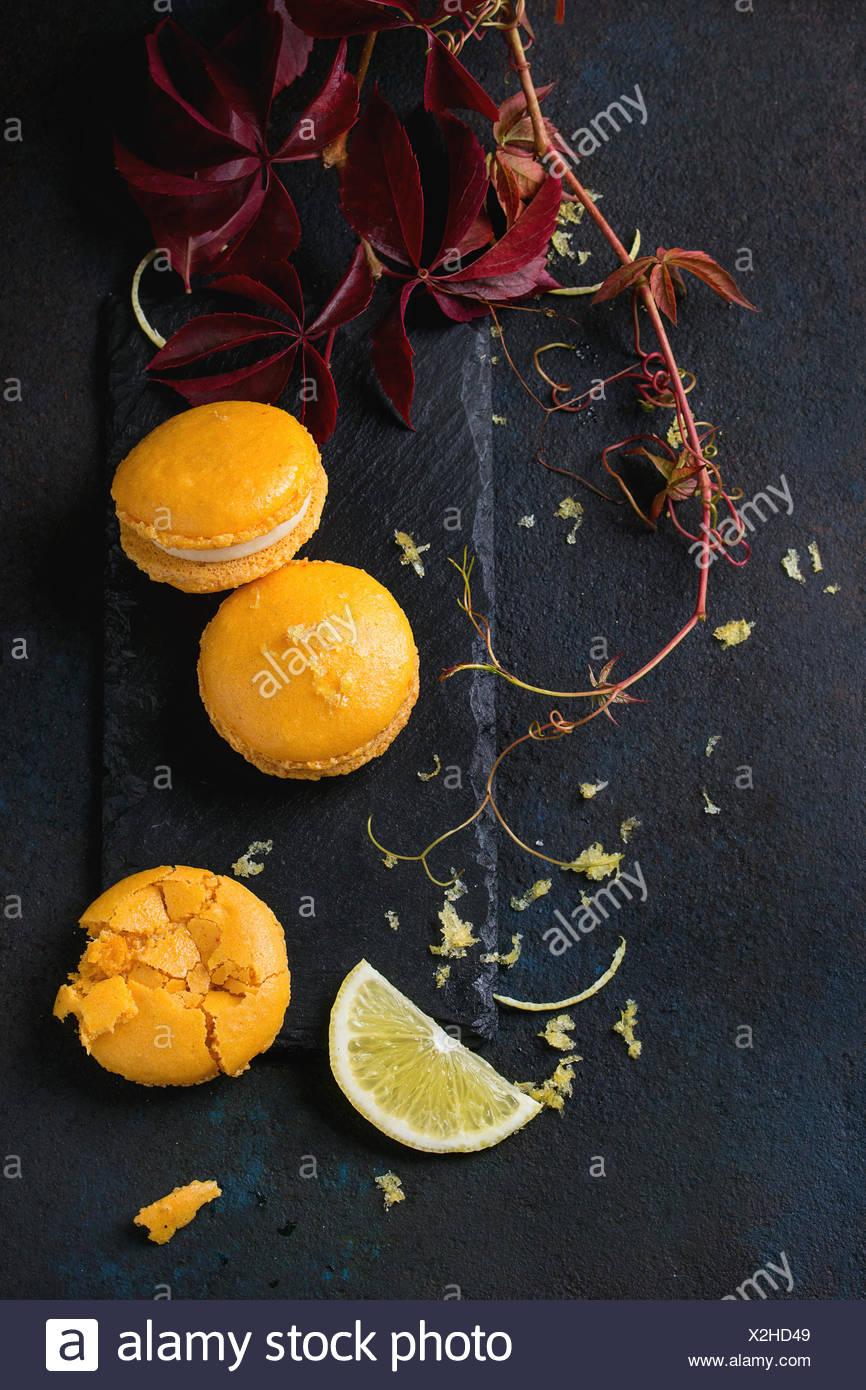 Ganze und gebrochene orange Zitrone hausgemachte Makronen mit weißer Schokolade, Zitronenscheibe und Lebensfreude, citrus Zucker auf Schiefer Brett mit au Stockbild