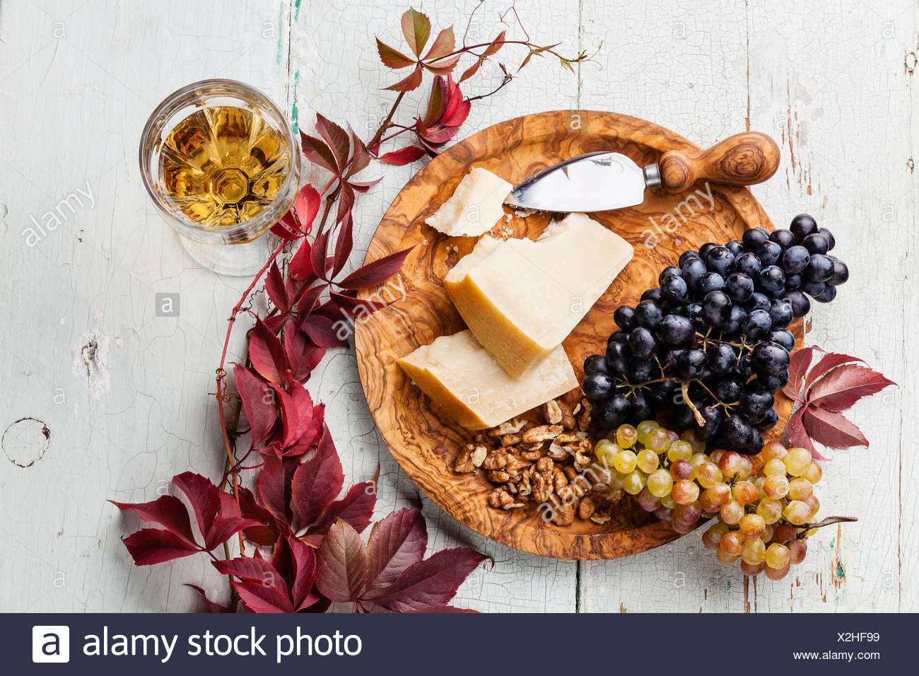 Parmesan-Käse und Trauben auf Oliven Holzplatte und Wein Stockbild