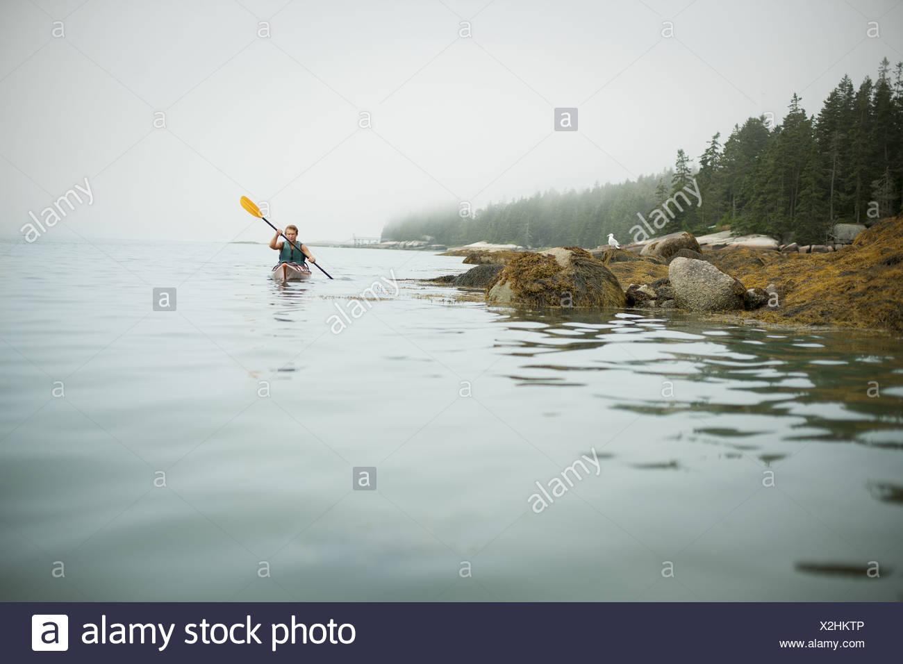 New York State USA Mann paddeln Kajak auf ruhigem Wasser nebligen Bedingungen Stockbild