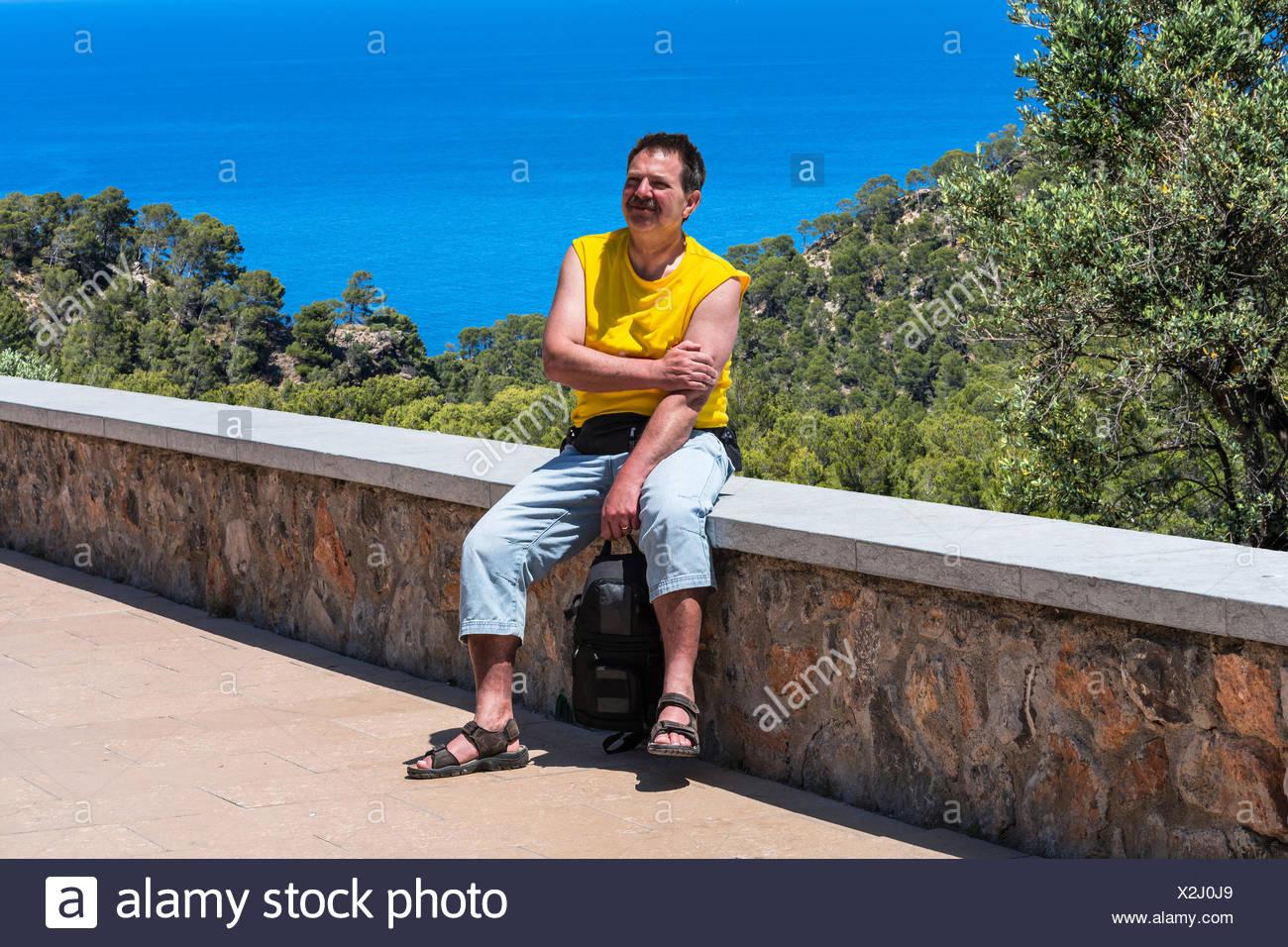 Ein Mann sitzt bei Sonneschein in einer Mauer im Hintergrund Pinienwald und das blaue Meer. Aufnahme in Mallorca, Spanien. Stockbild