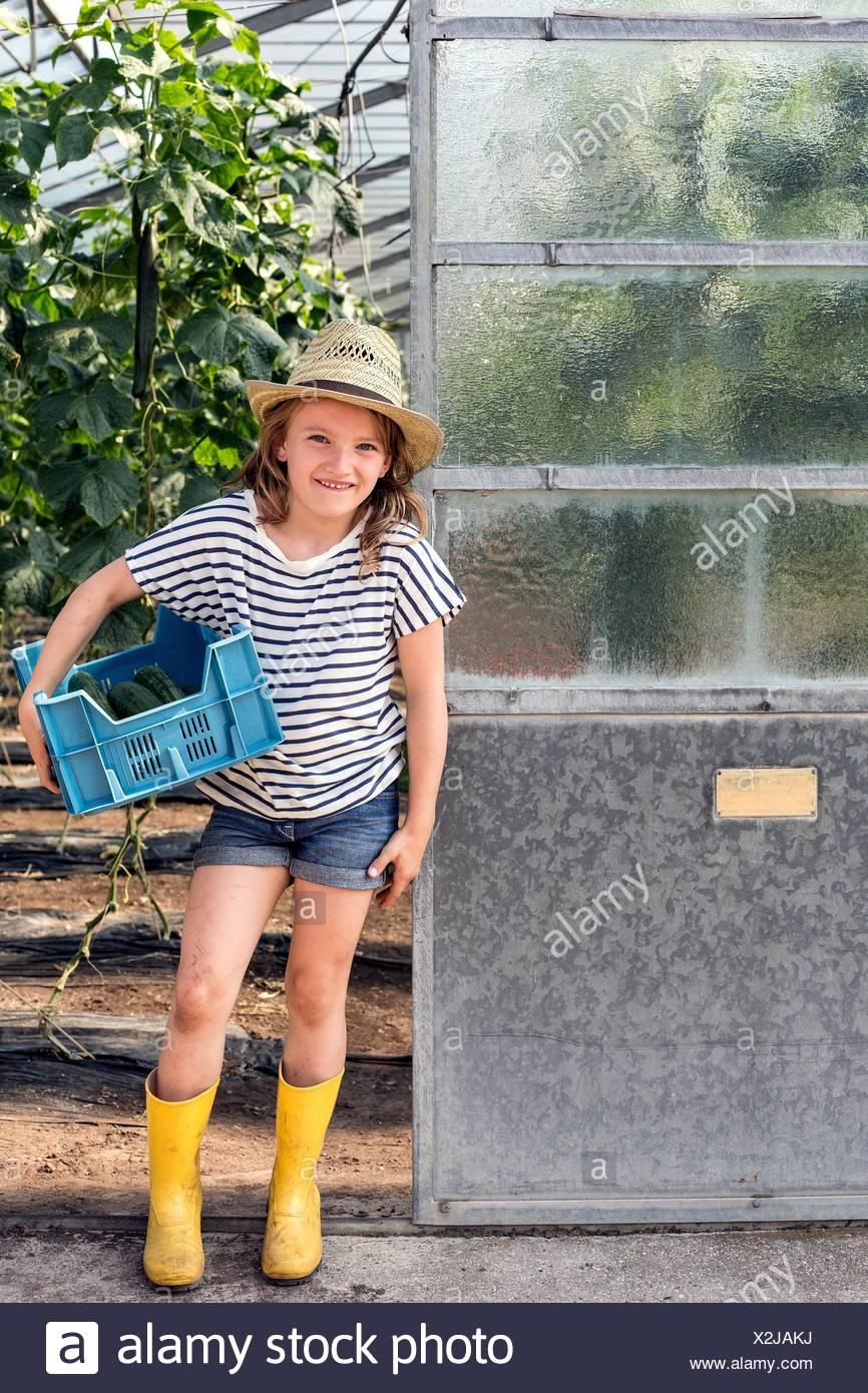 Mädchen tragen Gummistiefel und Hut stehen im Treibhaus Tür hält Tablett Blick auf die Kamera zu Lächeln Stockbild