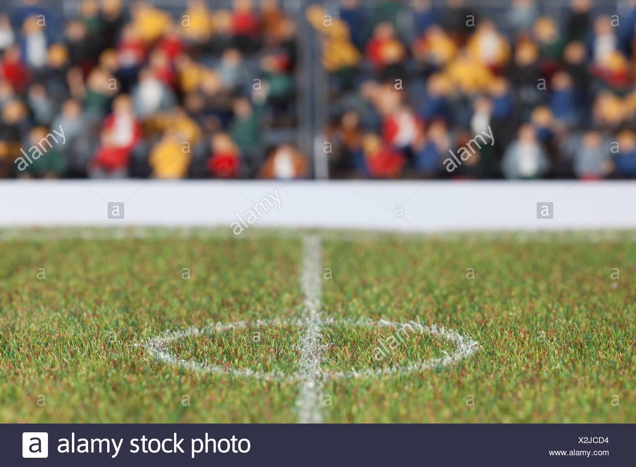 Das Mittelfeld wie ein Mini-Fußballfeld, Zuschauer Figuren im Hintergrund Stockbild