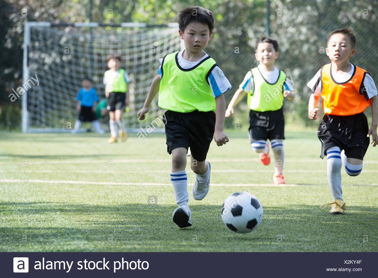 Die Jungs Fußball spielen auf dem Spielplatz Stockfoto