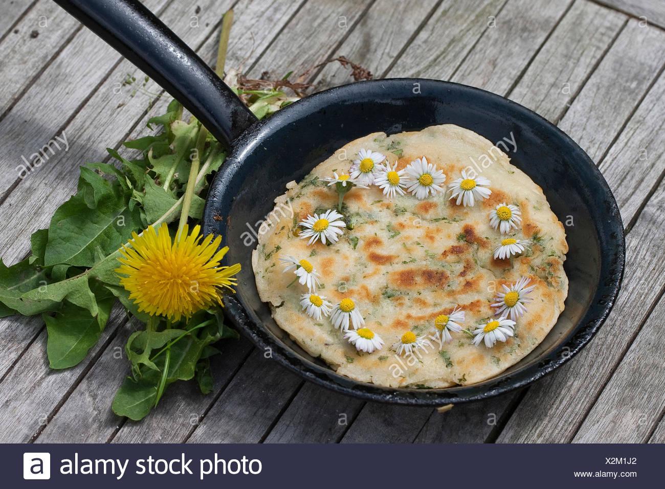 Pfannkuchen Sie mit Gänseblümchen und Löwenzahn in einer gusseisernen Pfanne, Deutschland Stockbild