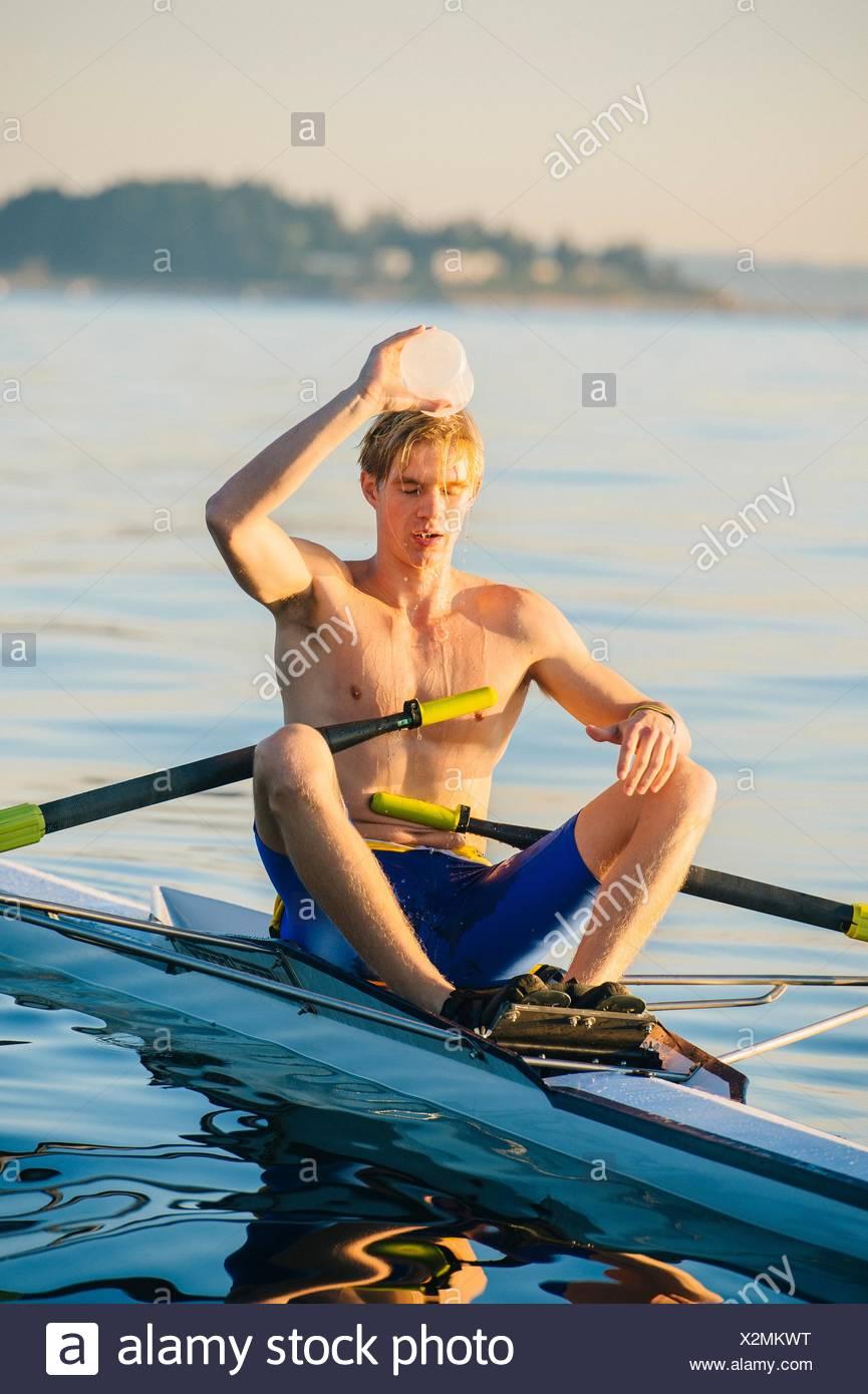 Teenager im Boot, Wriggen gießt Wasser über Kopf, um ihn abkühlen lassen Stockbild