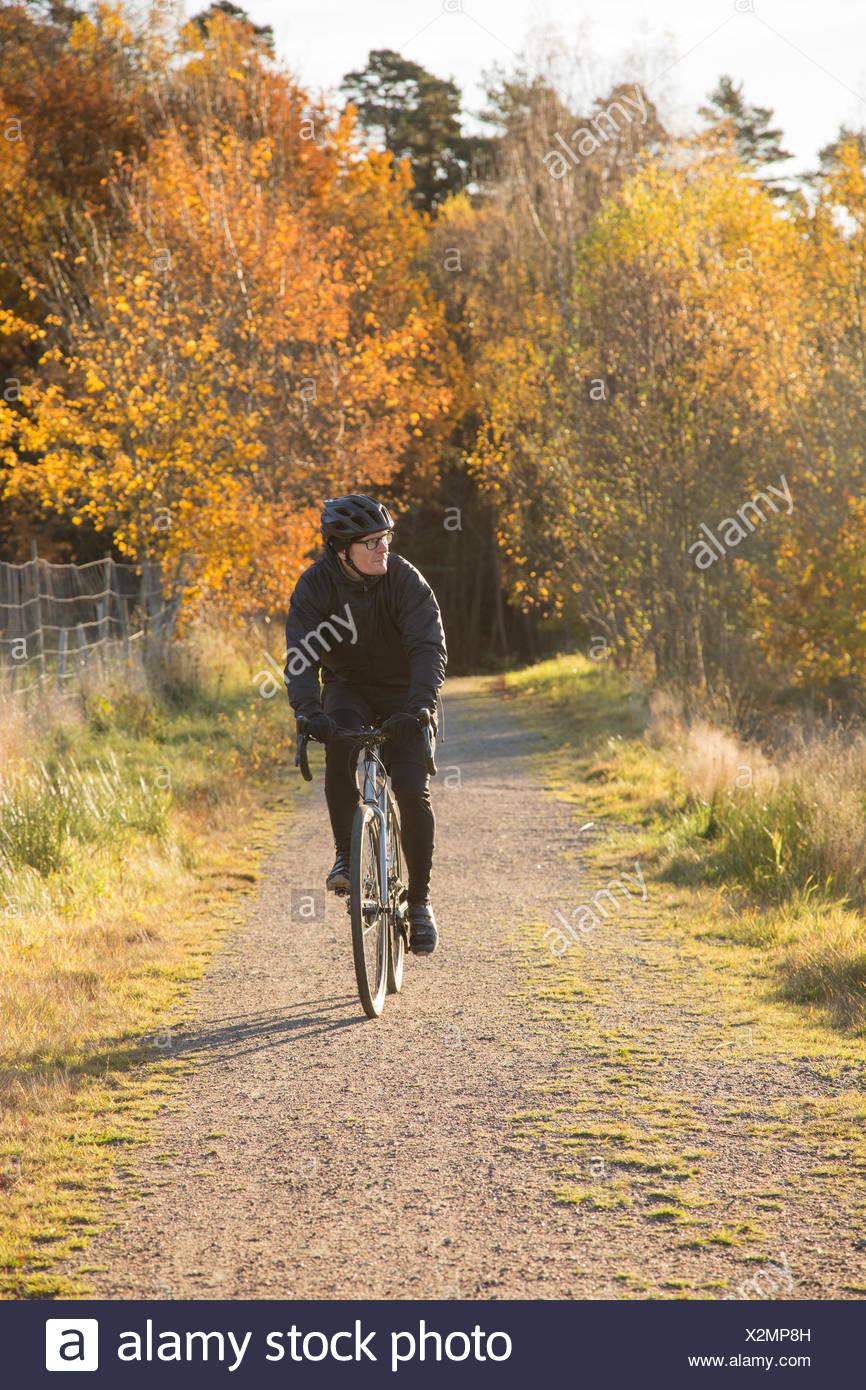 Schweden, vastergotland, lerum, reifer Mann reiten Fahrrad auf unbefestigte Straße durch Wald Stockbild