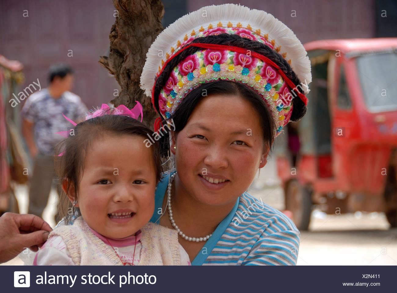 Porträt, Ethnologie, Frau der Volksgruppe Bai mit typischer Kopfbedeckung und ein Kleinkind, Yongning, Lugu Hu Seengebiet, Yunnan P Stockbild