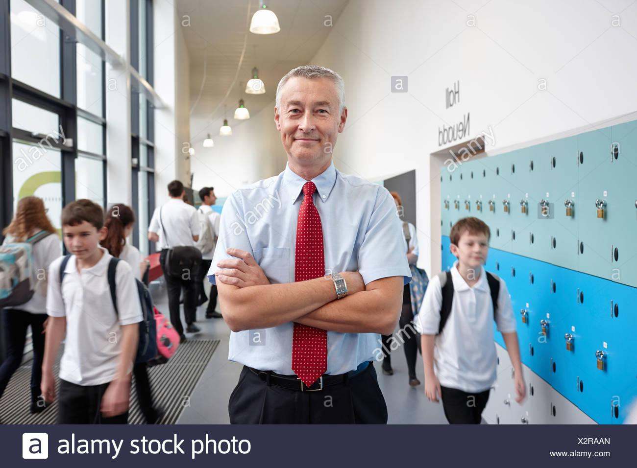Porträt von männlichen Lehrer mit auf Schule Flur verschränkten Armen Stockbild