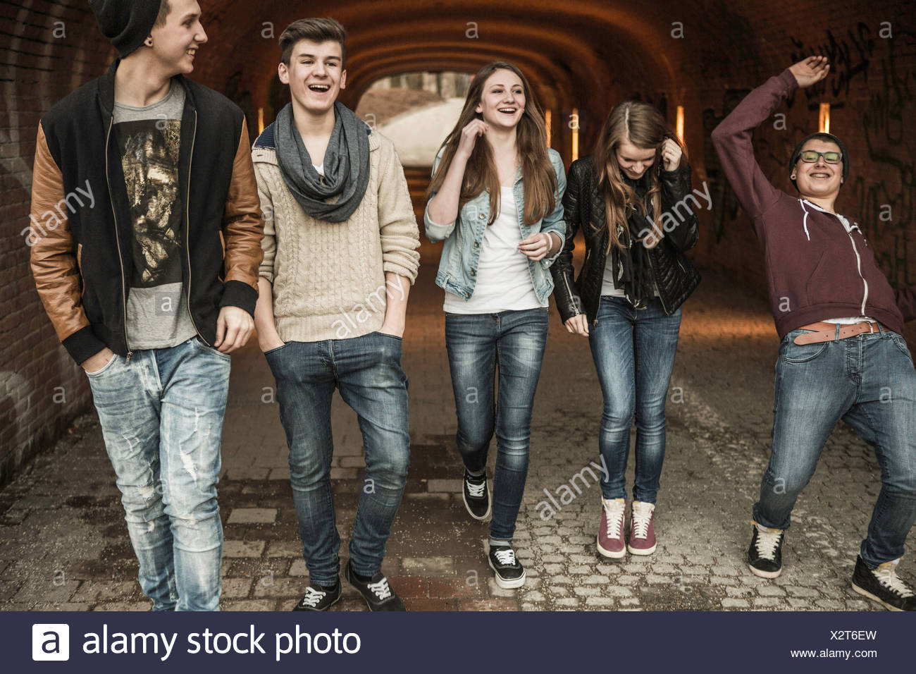Fünf Jugendliche zu Fuß durch Tunnel, lachen und scherzen Stockbild