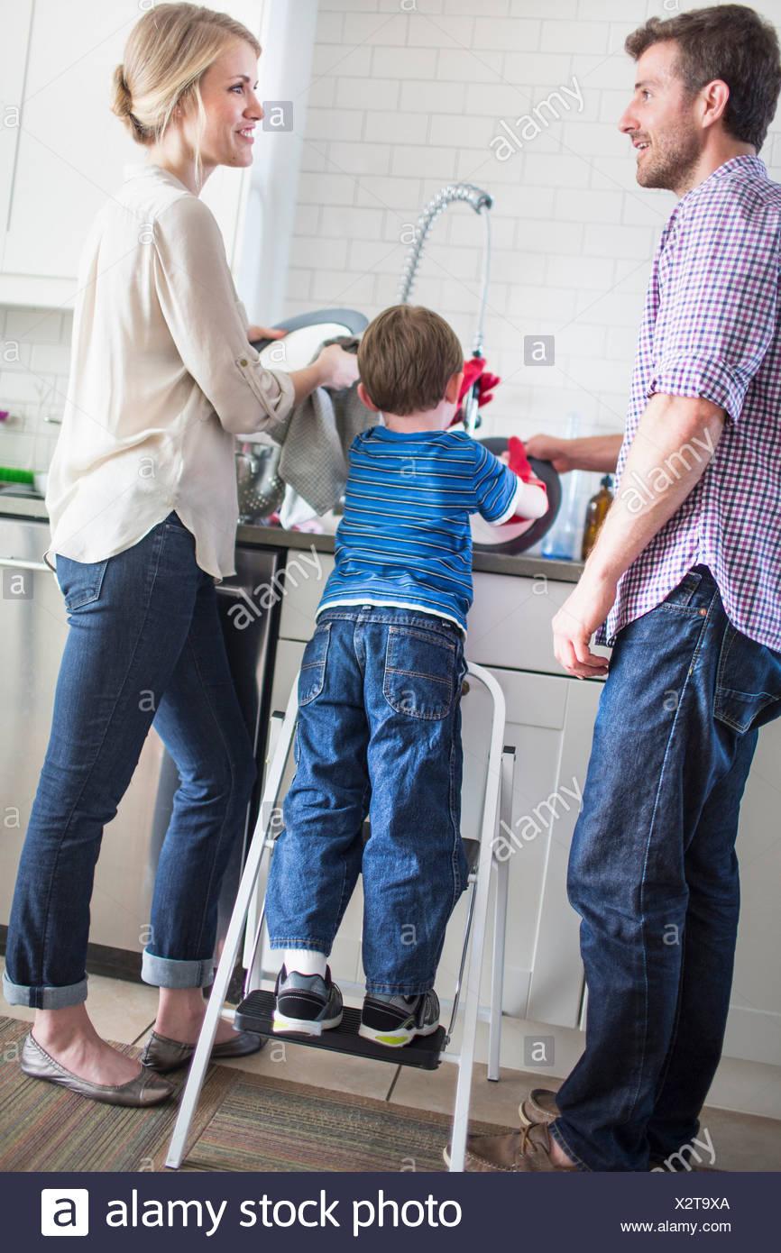 Eltern und Sohn beim Abwasch Stockbild