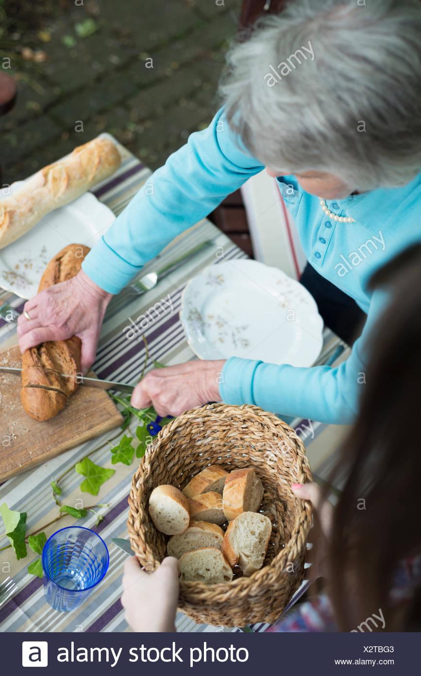 Ältere Frau Schneiden von Brot, hoher Winkel Stockbild