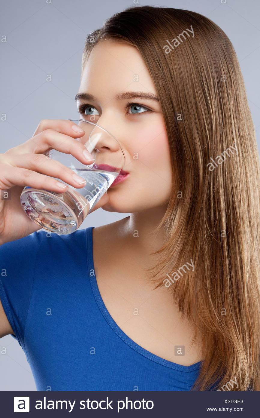 Eine Frau trinkt ein Glas Wasser Stockbild