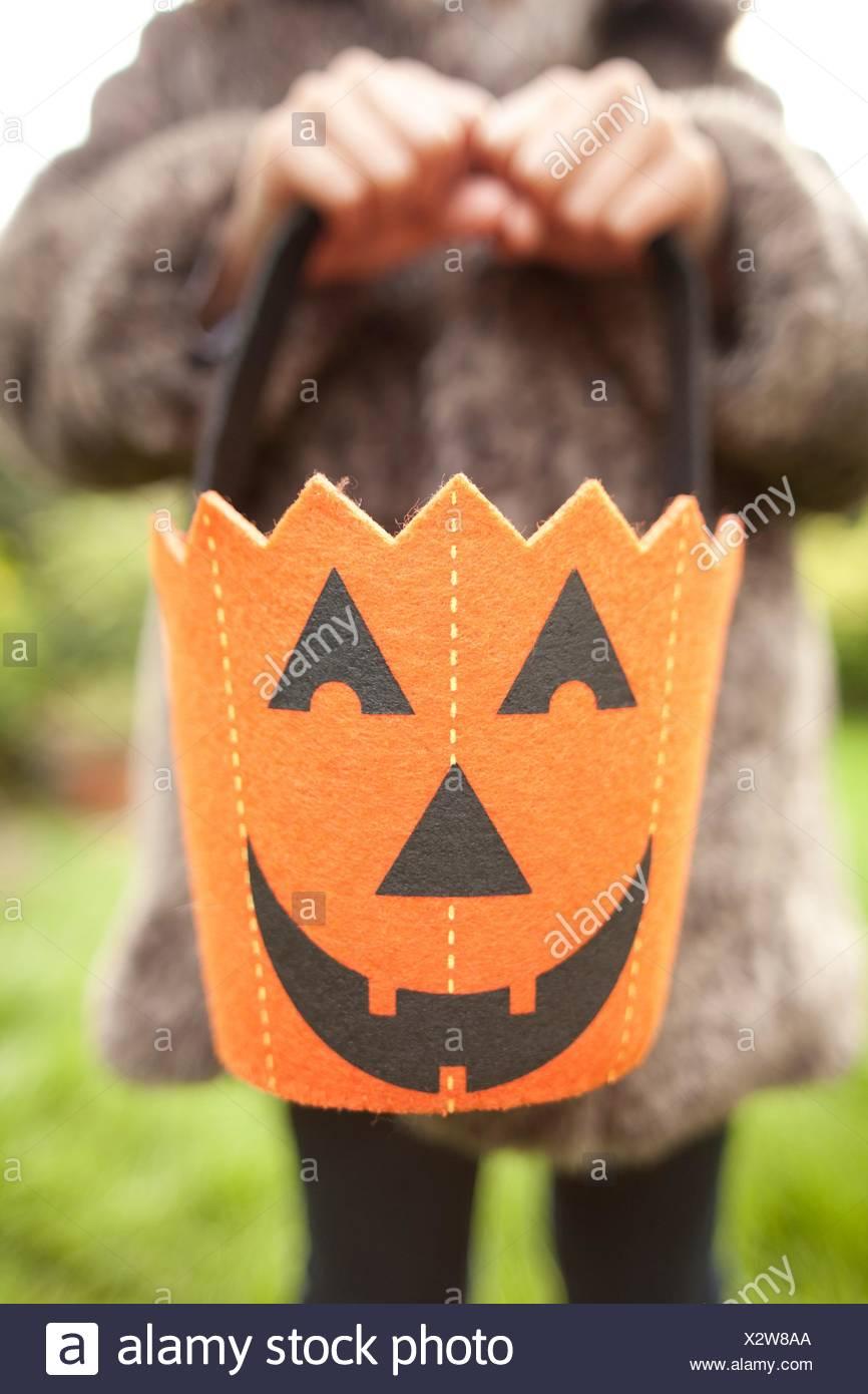 Mädchen hält Halloween Kürbis Tasche für Trick oder Behandlung von Stockbild