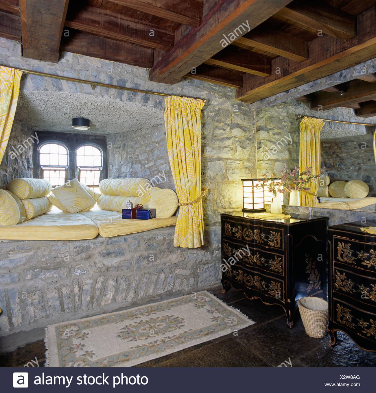 Gelbes Kissen auf Stein Fensterplatz im Badezimmer mit Steinmauern ...