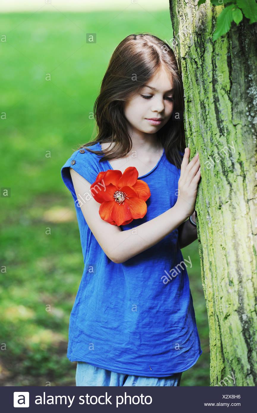 Mädchen lehnte sich gegen Baum im park Stockbild