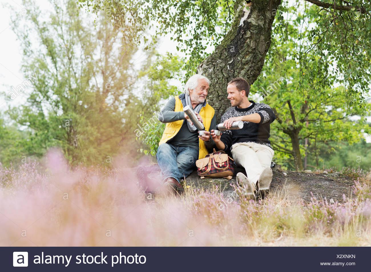 Vater und erwachsener Sohn Kaffee trinken aus der Flasche Stockfoto