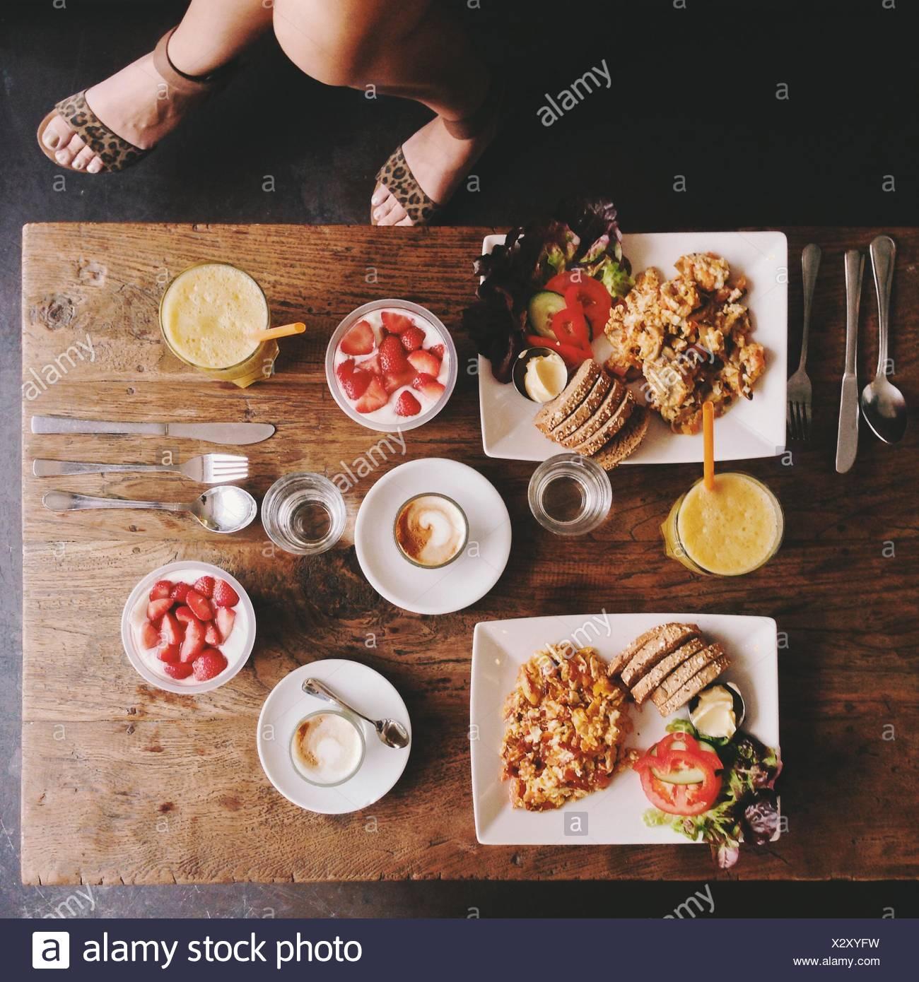 Draufsicht auf die Beine und Frau Frühstückstisch Stockfoto