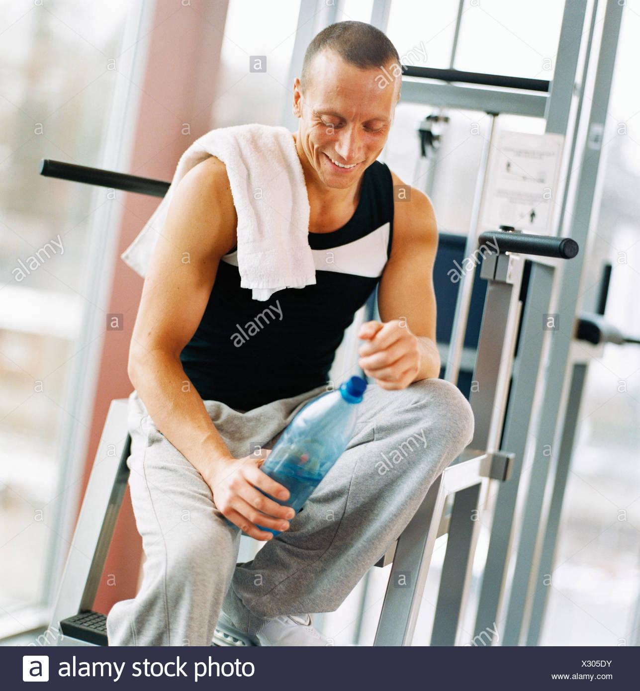 30-34 Jahre 45-49 Jahre Aktivität Erwachsene nur Sportler Bodybuilding Flasche Flasche Wasser Farbbild Ausübung Turnhalle glücklich Stockbild