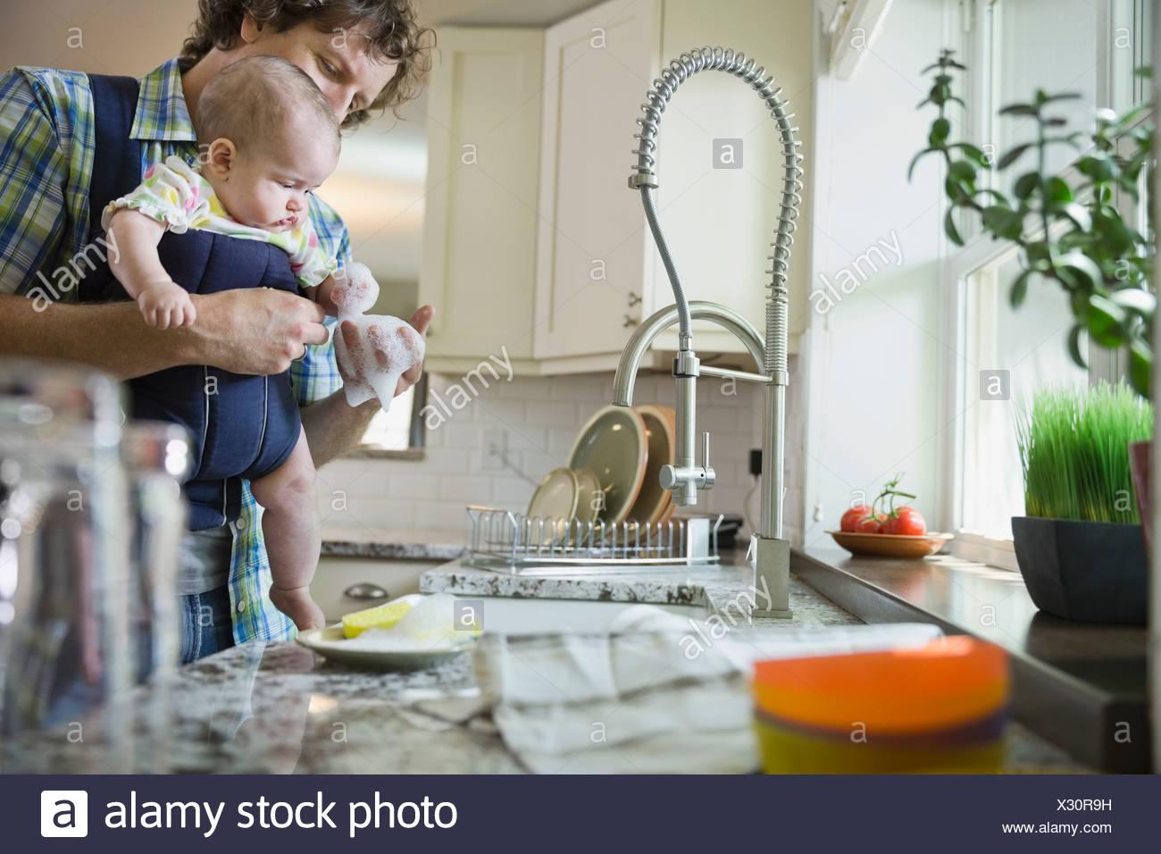 Vater halten Babymädchen beim Abwasch Stockbild