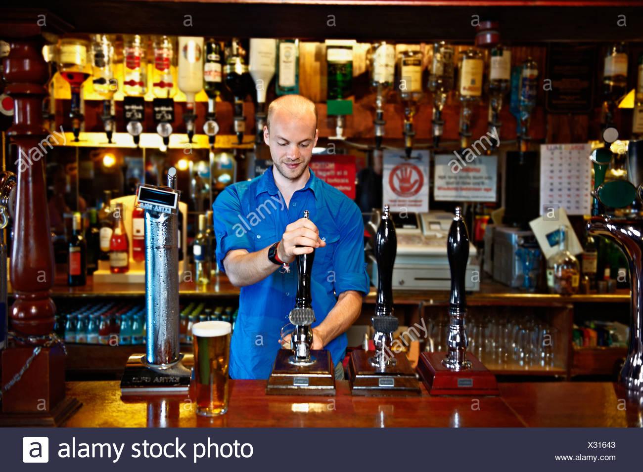 Barmann stehend hinter bar im Pub Stockbild