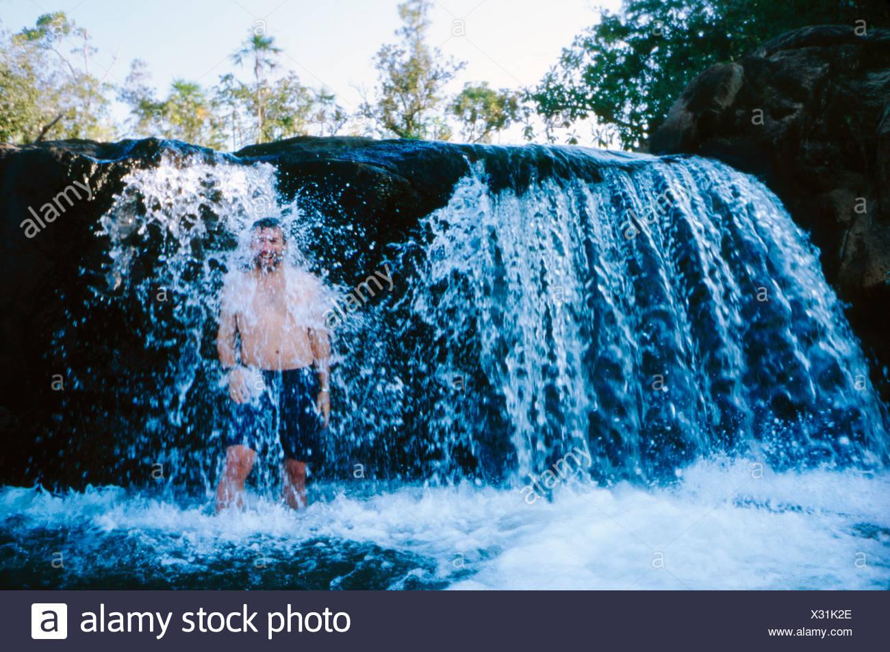 Rio Am Pool, Mountain Pine Ridge Ein Mann Stehend Unter Wasserfall Stockbild