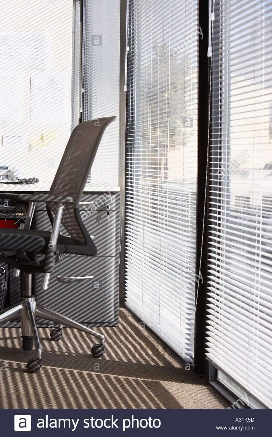 Bürostuhl mit horizontalen Jalousien auf großen Fenstern Stockbild