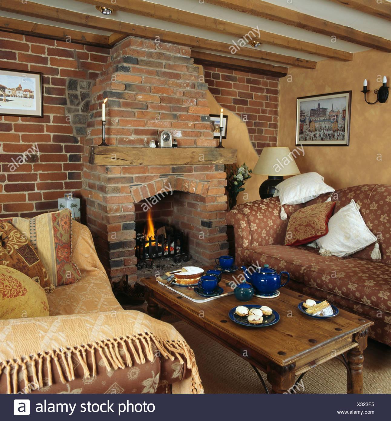 sofas auf beiden seiten des indonesischen couchtisch vor gemauerten kamin mit brennenden feuer. Black Bedroom Furniture Sets. Home Design Ideas