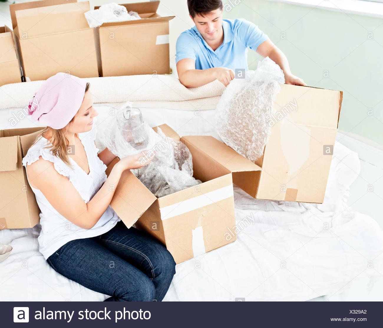 Glückliches junges Paar Auspacken Boxen mit Brille Stockbild
