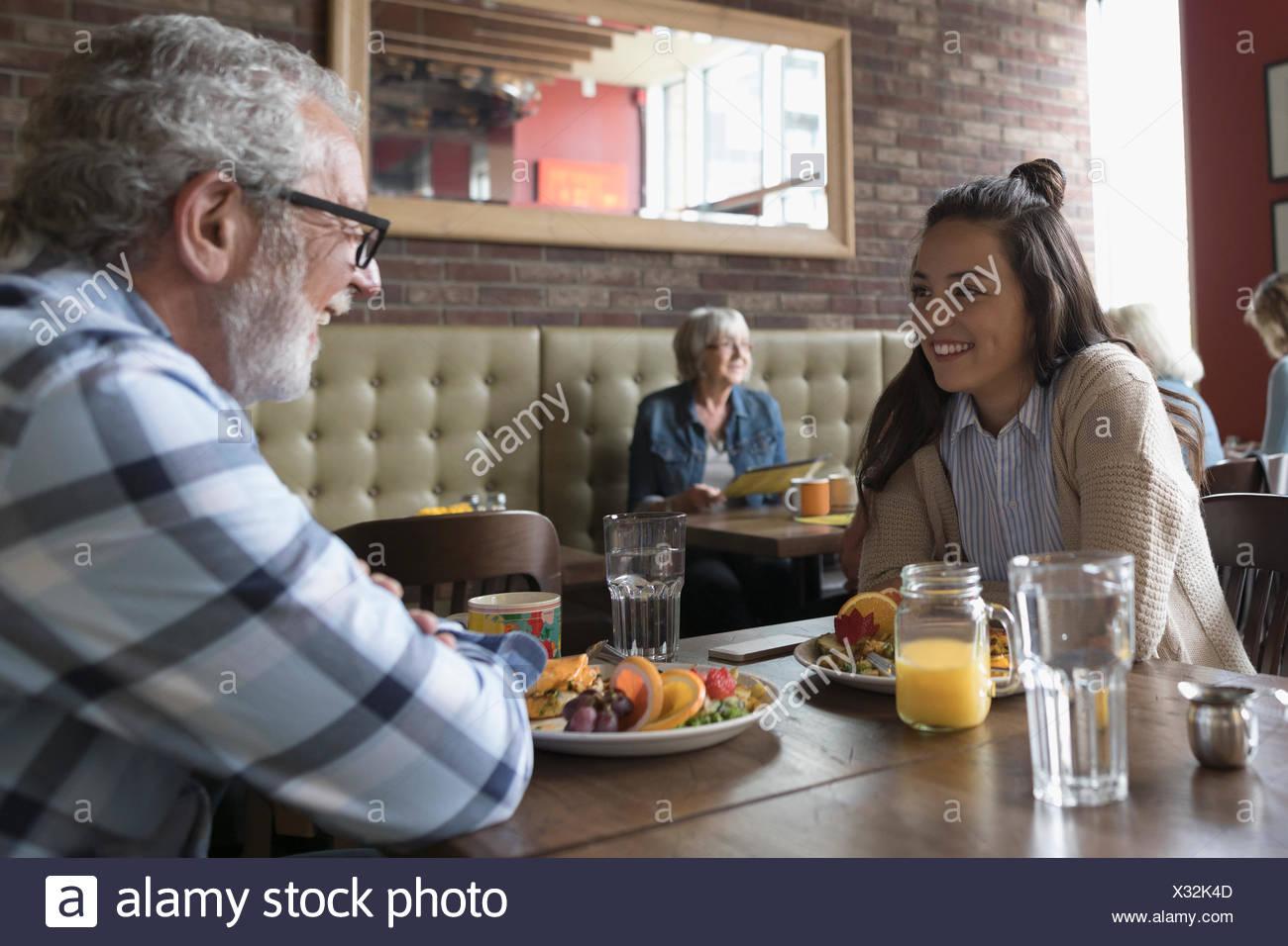 Großvater und Teenager Enkelin sprechen, Essen Brunch an Diner Tisch Stockbild