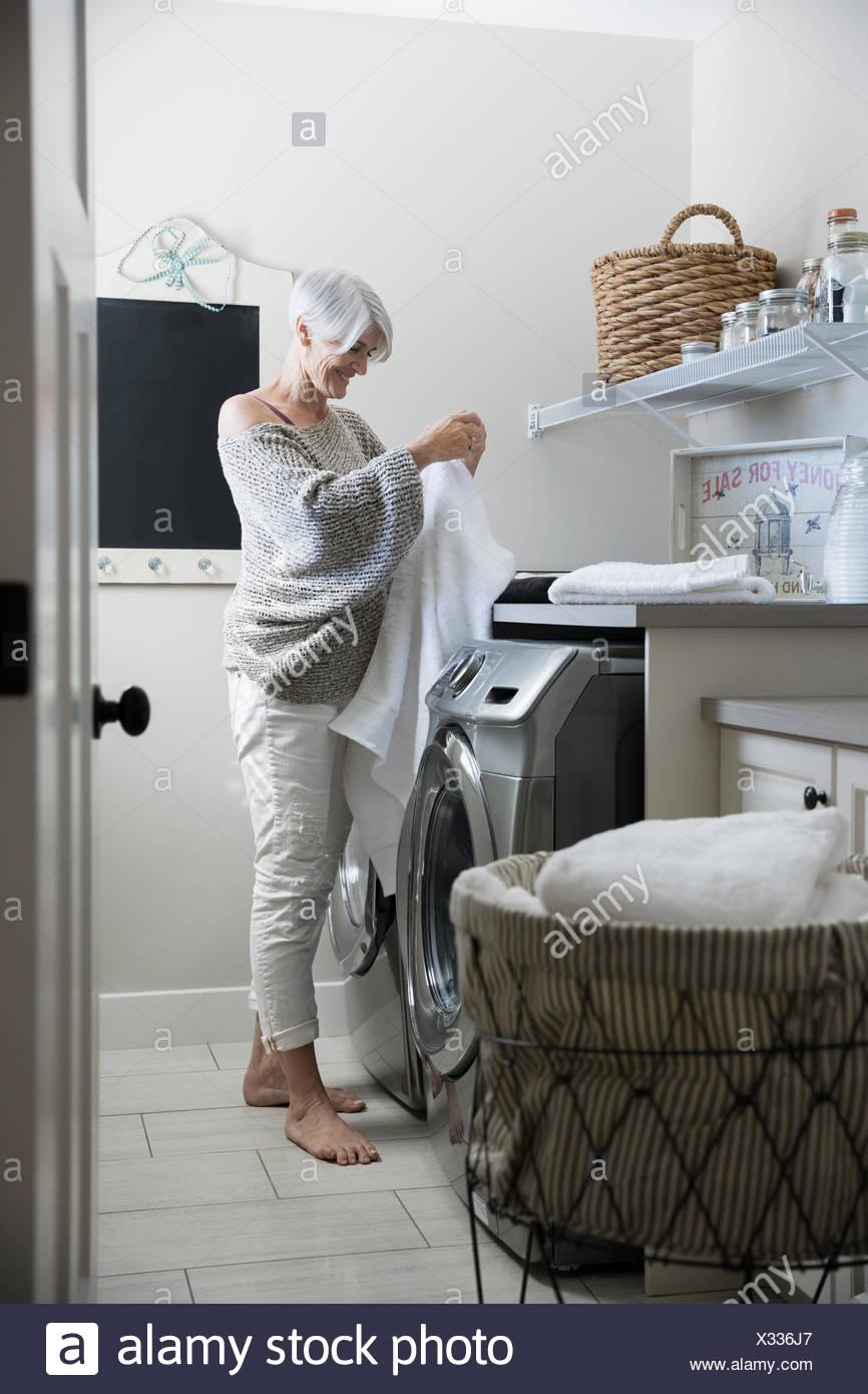 Frau Falten Handtücher in Waschküche Stockbild