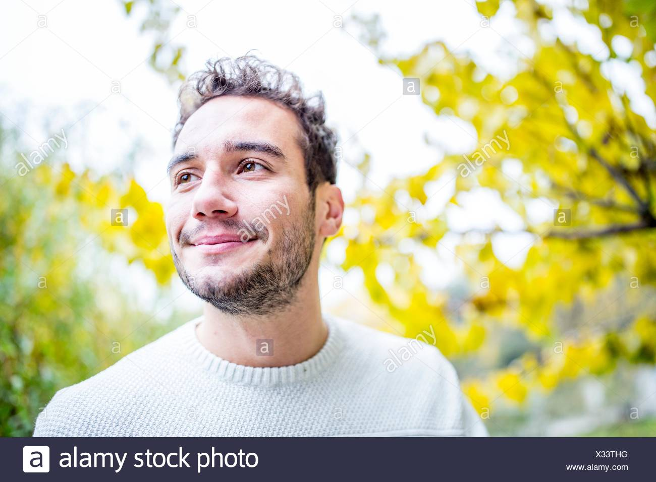 -MODELL VERÖFFENTLICHT. Junger Mann wegsehen und lächelnd, close-up. Stockbild
