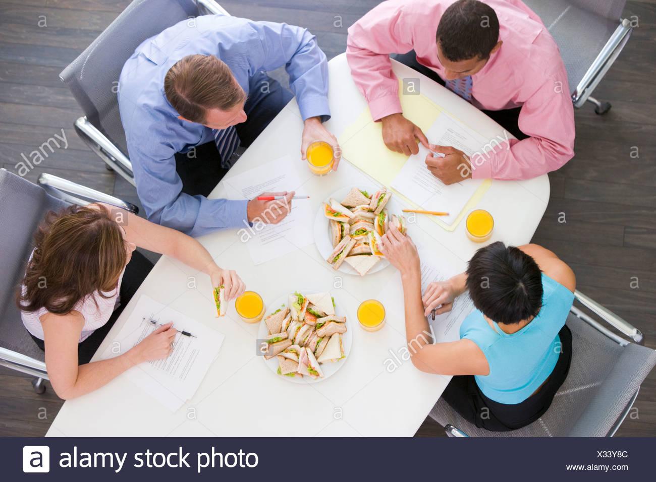 Vier Unternehmer am Konferenztisch mit sandwiches Stockbild
