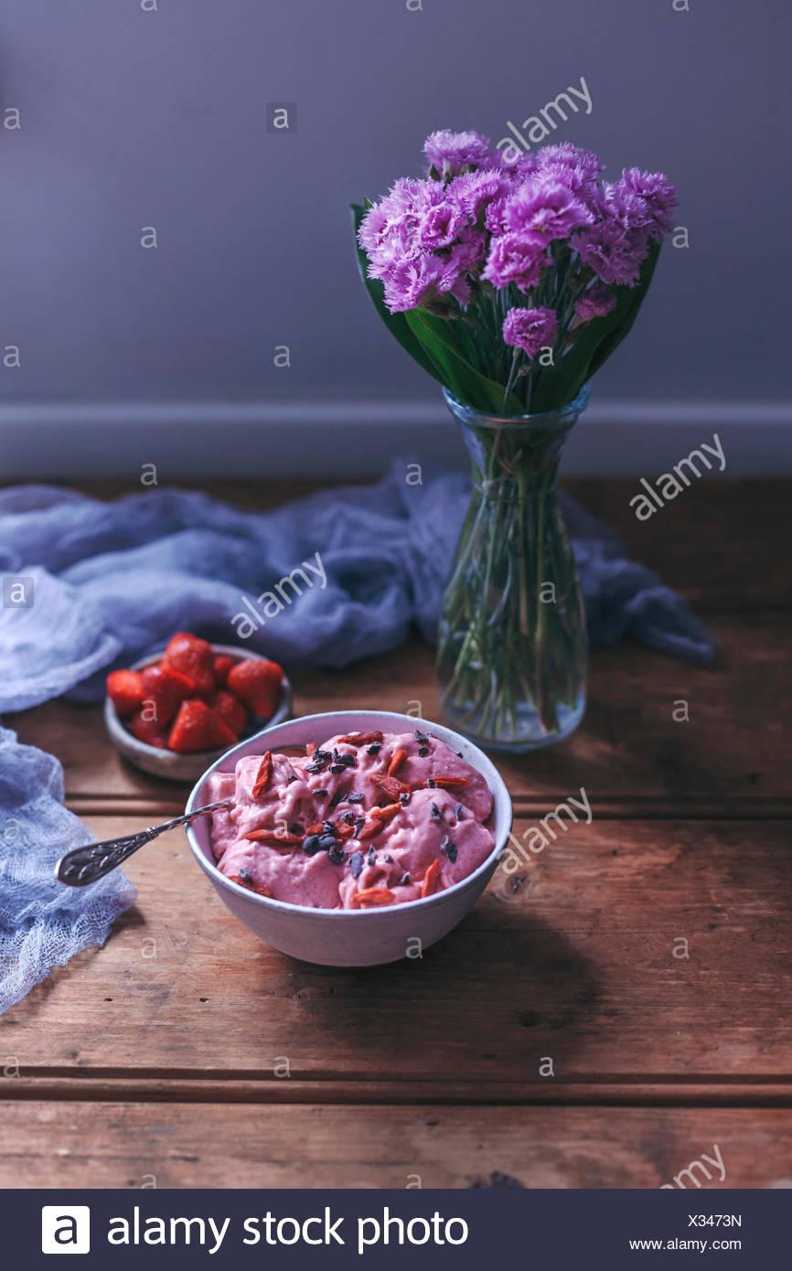 Erdbeer-Banane Eis in eine Schüssel geben, garniert mit Goji-Beeren und Kakaonibs Stockfoto