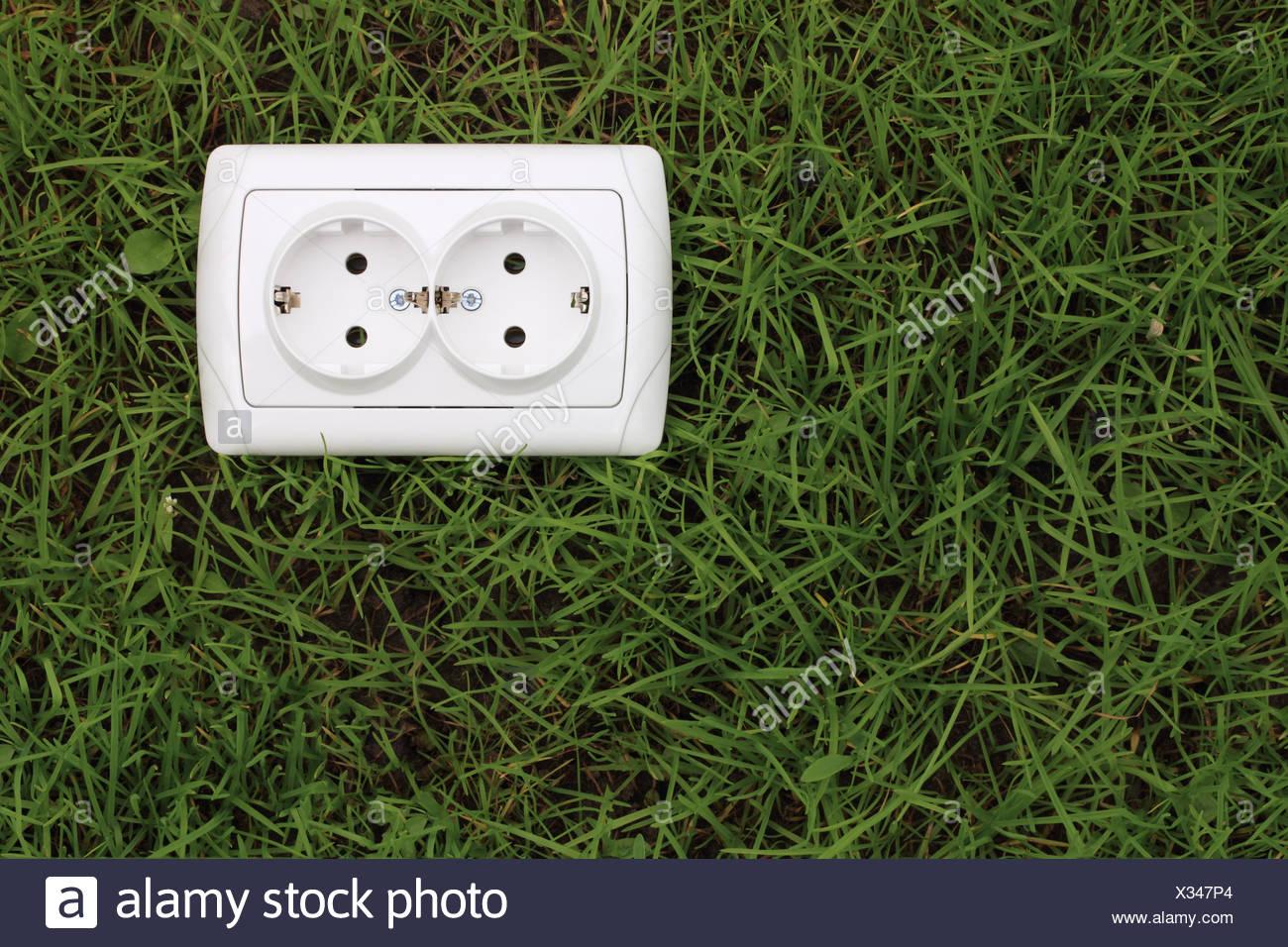 elektrische Steckdose auf einem grünen Rasen-Hintergrund Stockbild