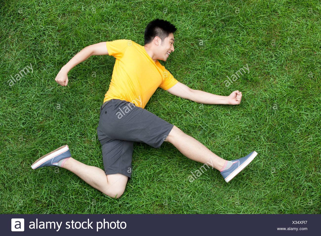 Kreative junge Mann imitieren laufen auf Wiese Stockbild