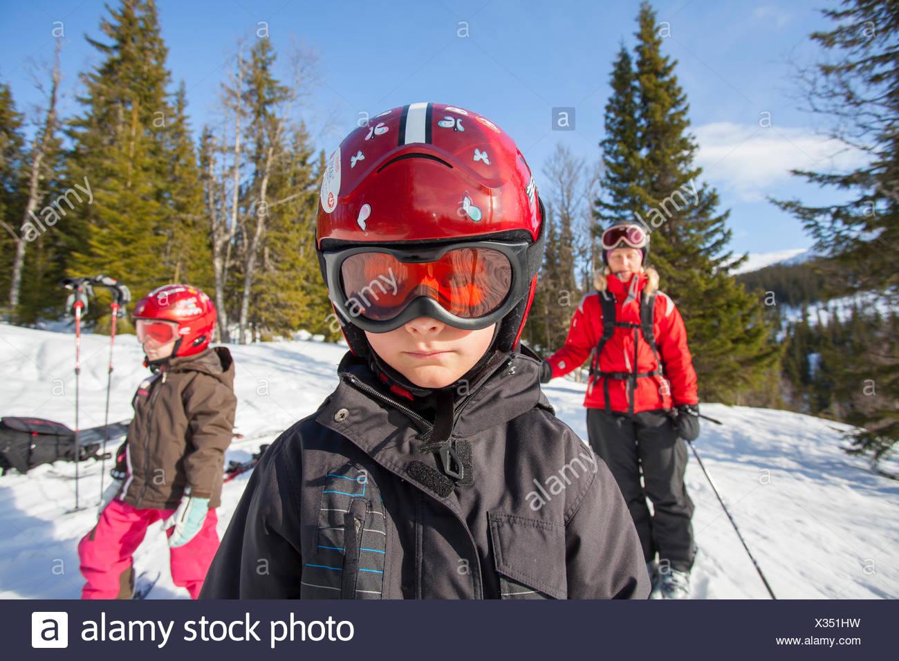 Norwegen, Osterdalen, Trysil, Mutter und ihre zwei Kinder (4-5, 8-9) hinunter Skipiste Stockbild
