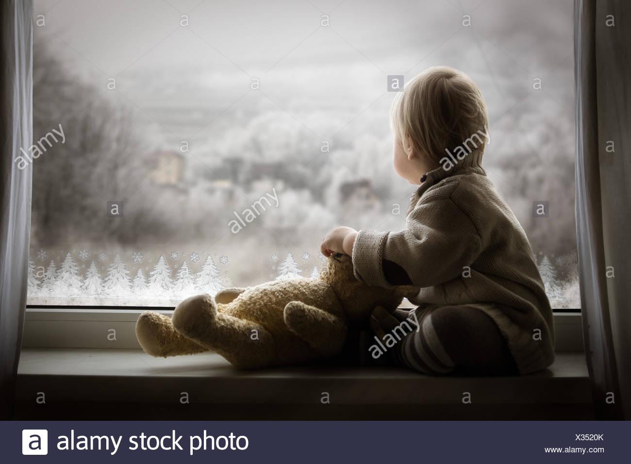 Junge sitzt auf der Fensterbank mit Teddybär und Fenster Stockbild