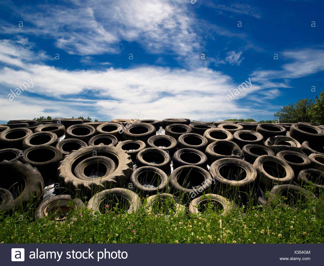 Alten Bauernhof-Reifen in einem Stapel im Freien unter blauem Himmel Stockbild