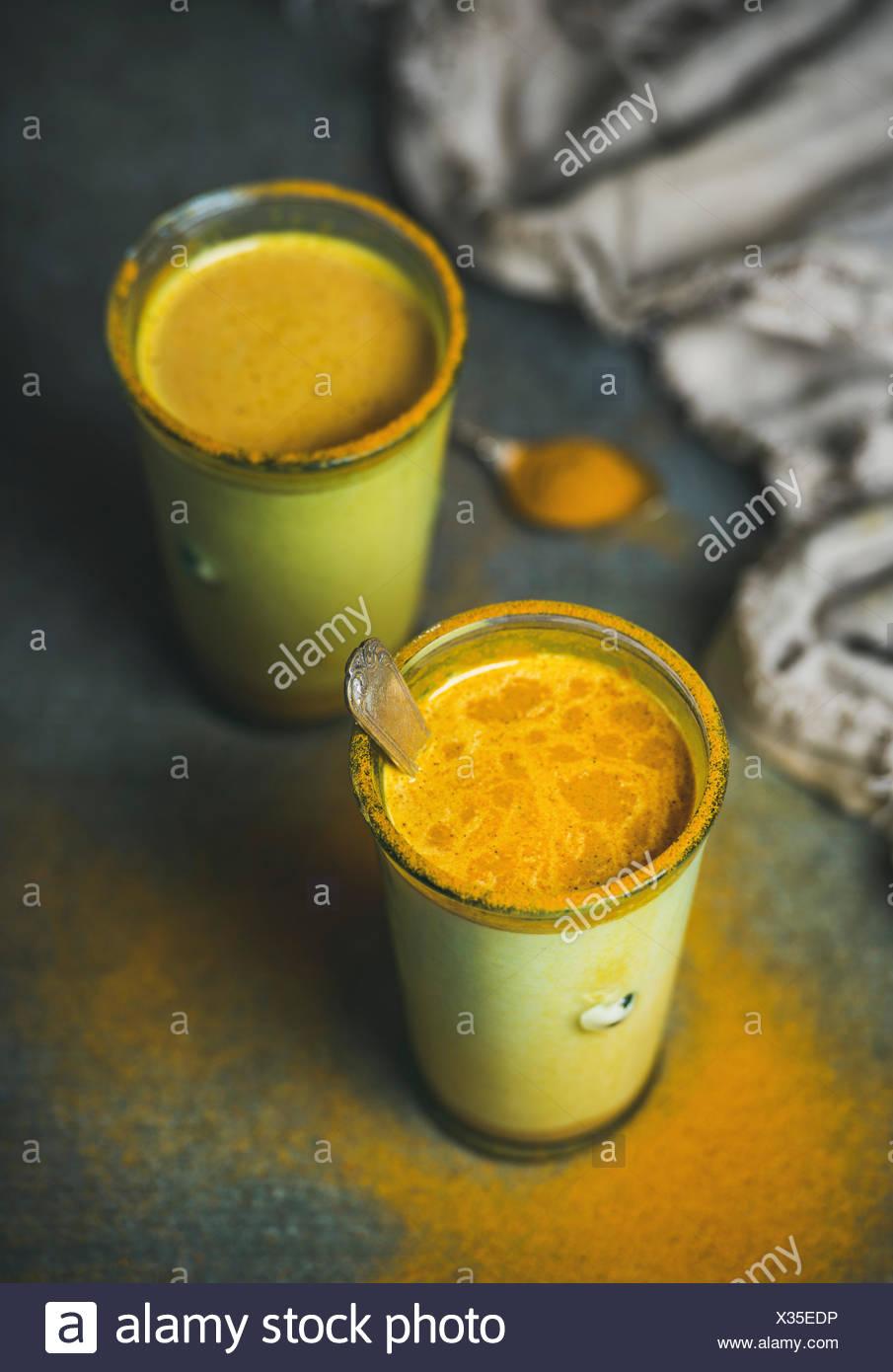Goldene Milch mit Kurkuma-Pulver in Gläsern auf dunklem Hintergrund. Gesundheit und Energie fördernde, Grippe Heilmittel, natürliche kalten Getränk zu kämpfen. Sauber, Essen, d Stockbild