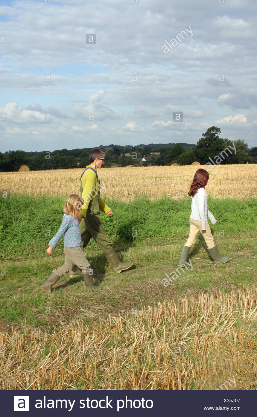 Mutter zu Fuß durch ein Feld mit ihren beiden Töchtern in Landschaft von Sussex England Stockbild
