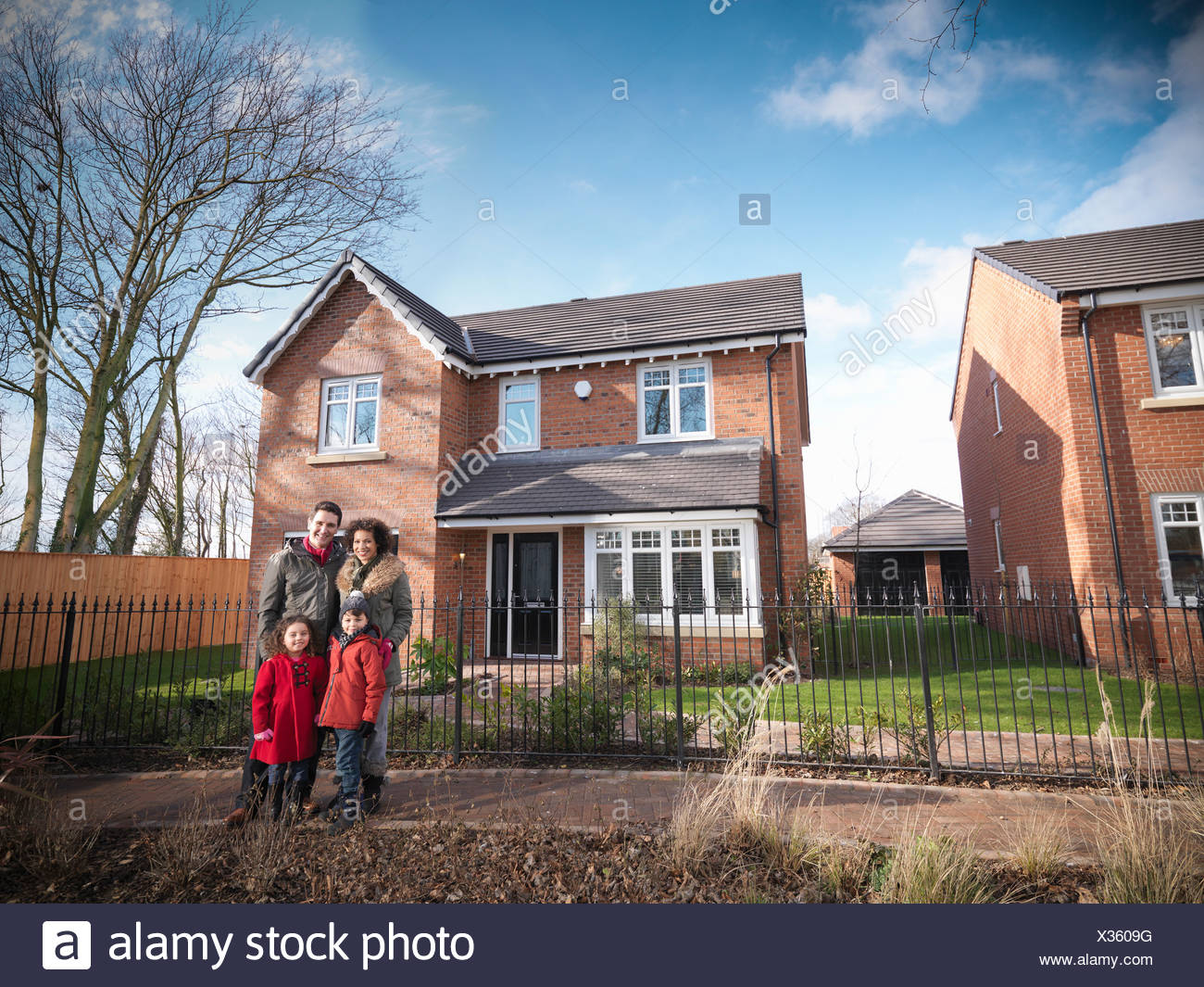 Familie lächelnd vor Haus Stockbild