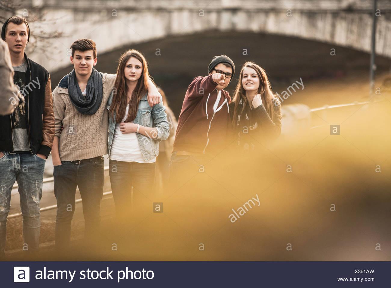 Fünf Jugendliche im Freien, junge zeigt auf Kamera Stockbild