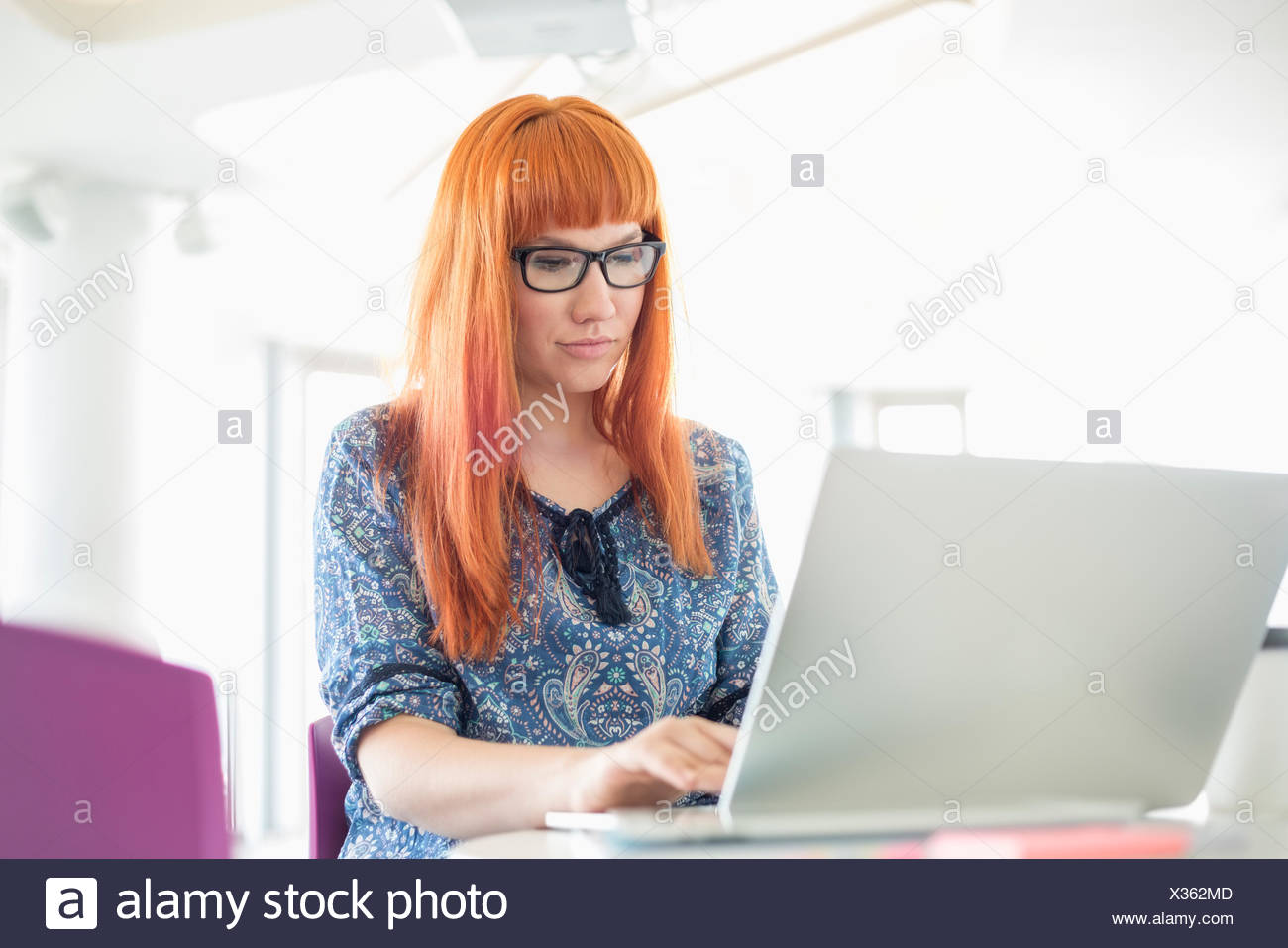 Geschäftsfrau, die Arbeiten am Laptop in Kreativbüro Stockbild