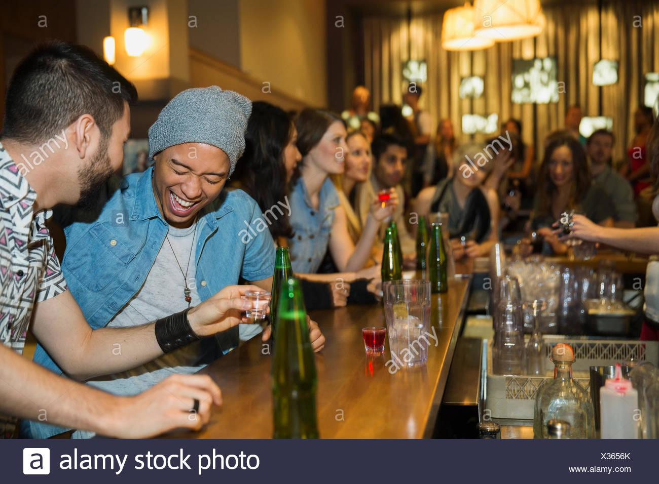 Freunde lachen und dabei in Aufnahmen Bar Stockbild