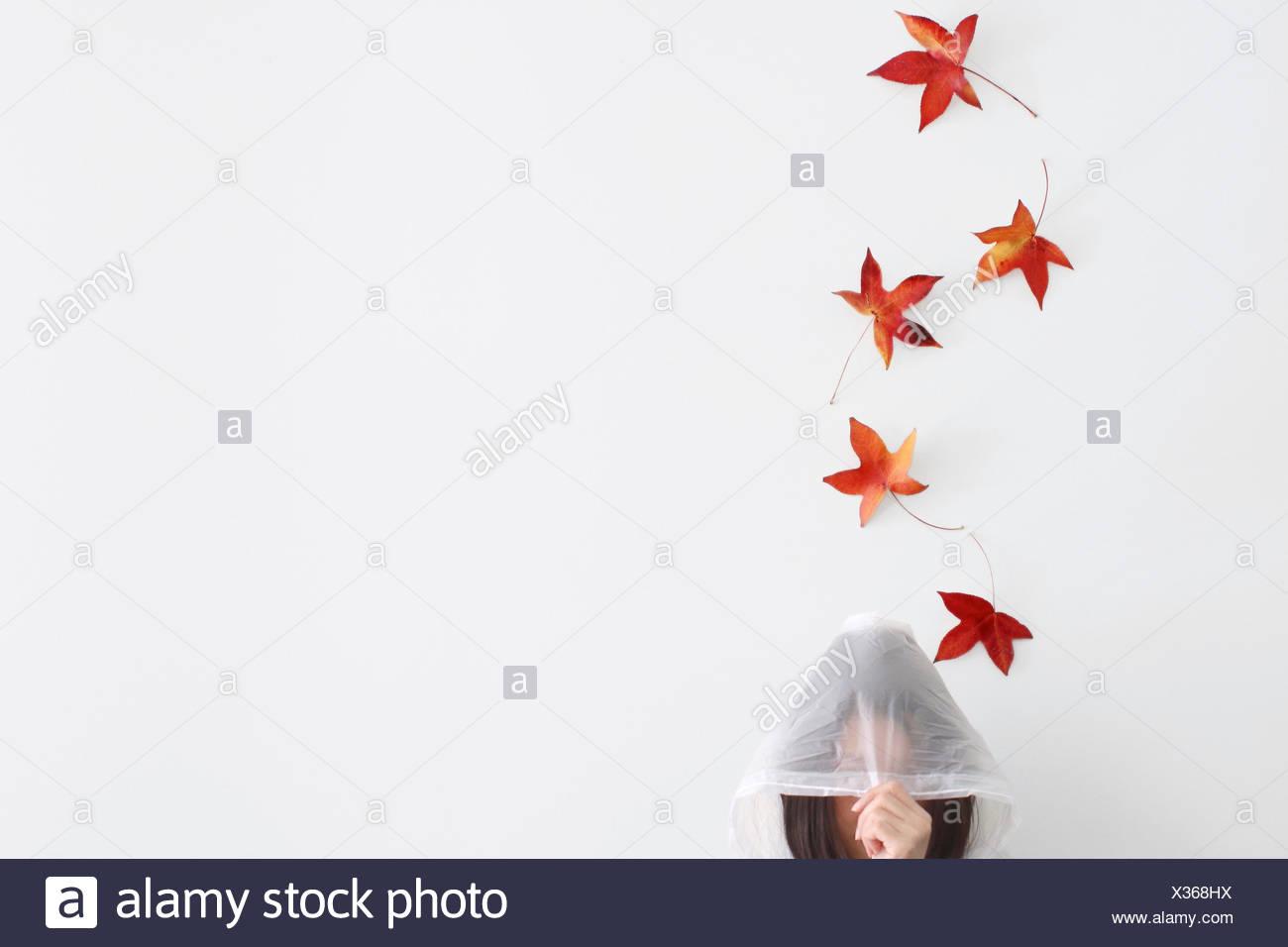 Herbstblätter fallen auf eine Frau trägt einen Regenmantel Stockbild