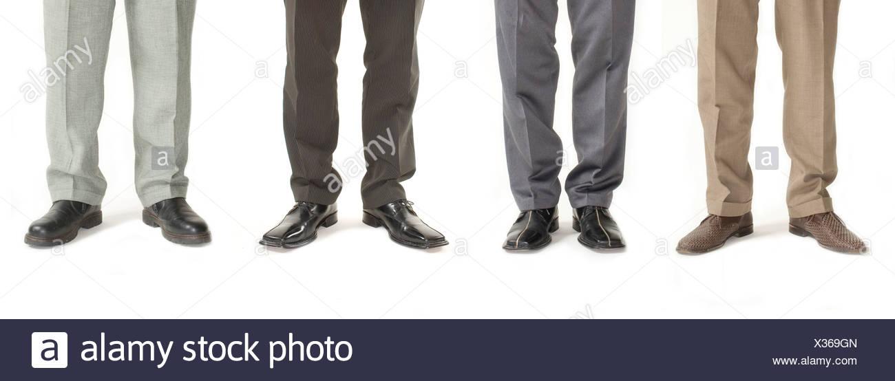 Vier Unternehmer stehen in einer Reihe, Detail der Beine Stockbild