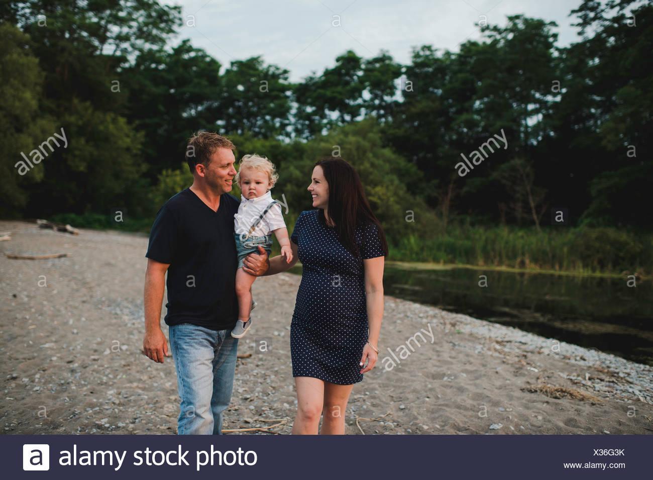 Schwangere Paar am Strand mit männlichen Toddlersohn, Lake Ontario, Kanada Stockbild