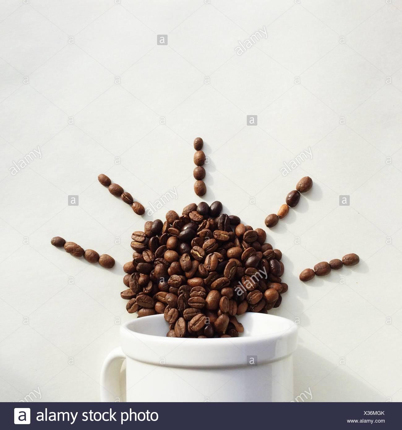 Kaffeebohnen, die aus einer Tasse in der Form der Sonne Stockbild